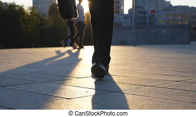 Feet of businessman with briefcase walking in city street at sunset time. Businessman commuting to work. Confident guy being on his way to office. Worker going outdoor. Front view Close up Slow motion