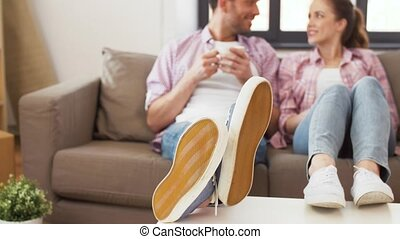 feet of couple drinking coffee at new home - moving, people...