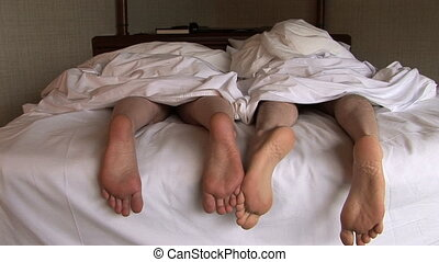 Feet of Couple in Bed - Couple in bed playing footsie, ...