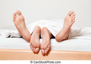 feet of couple in bed.