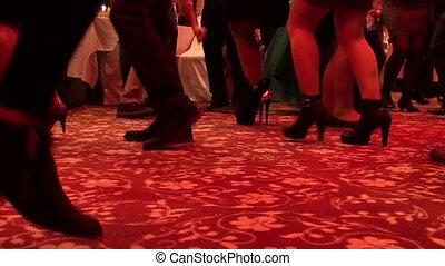 Feet of dancing people indoors