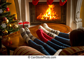 Feet of family in woolen socks warming at burning fireplace...