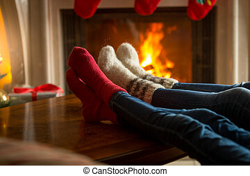Feet of family in woolen socks warming near burning fireplace at living room