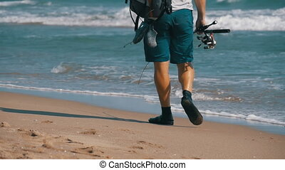 Feet of Fisherman with fishing rods and a backpack walks along the beach of the sea shore. Slow Motion