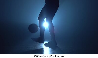 Feet of football player are stuffing the ball in twilight. -...