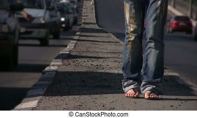 feet of girl dancing on highway middle in bust street of...