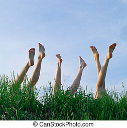 Feet of girls laying and sunbathing in a grass