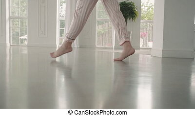 Feet of graceful woman walk on tiptoe at home or hotel before wedding. Young female run in pajamas in big room. Happy feminine legs in white interior. Concept joy, marriage.