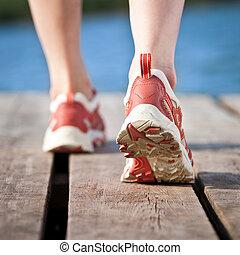 Feet of jogging person on wooden bridge