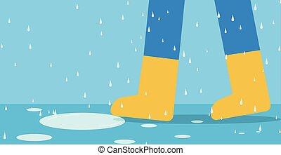 Feet of man in rain boots walk on road with rain