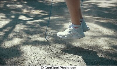 Feet of man jumping with a rope, boxing workout outdoors at...