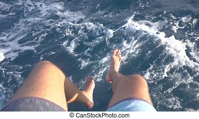 Feet of man on a moving boat above sea water