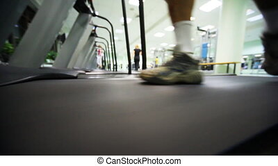 feet of man quickly go on treadmill at large gym, distance...