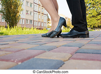 feet of men and women on a walk in the park