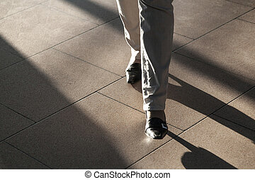 feet of people hurrying in the airport with sown shadows