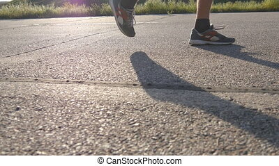 Feet of strong man running on road in summer. Male legs jogging during workout training on country route at sunset. Young man is training on an empty asphalt path. Working out outdoors, close up.