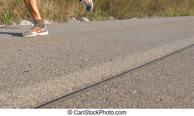 Feet of strong man running on road in summer. Male legs jogging during workout training on country route at sunset. Young man is training on an empty asphalt path. Working out outdoors, close up