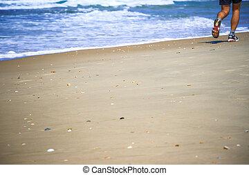 feet of the man running along the seashore