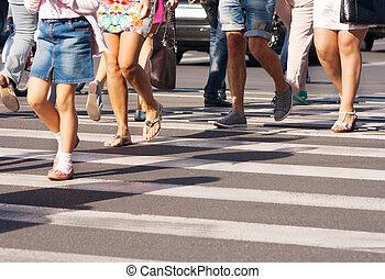 feet of the pedestrians crossing on city street