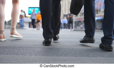 Feet of two businessmen crossing road in downtown. Legs of male coworkers walking a crosswalk in big city. Young colleagues commuting to work together. Blurred motion. Rear view Slow motion Close up