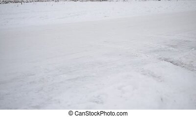 Feet of two men jogging in winter on white snowy road