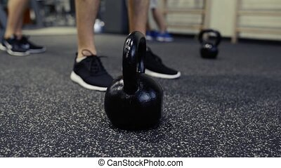 Feet of unrecognizable people and kettlebells on the floor.