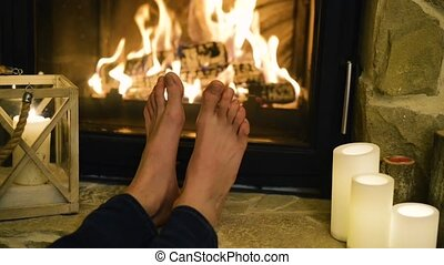 Feet of unrecognizable woman in front of the fireplace. -...