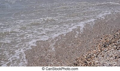 Feet of woman and girl walking on sandy beach