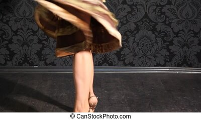 feet of woman dressed in skirt with frills dances - feet in...