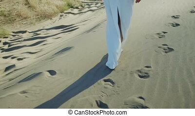 Feet of woman walking on beach dunes in white dress while sun drops shadow
