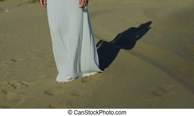 Feet of woman walking on beach dunes in white dress while sun drops shadow slow motion