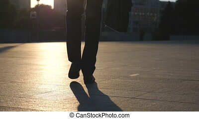 Feet of young businessman with a briefcase walking in city street. Business man commuting to work. Confident guy in suit being on his way to work. Cityscape backround. Slow motion Rear view Close up