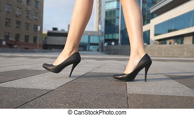 Feet of young businesswoman in footwear on high-heeled going...