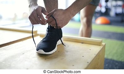Feet of young man tying shoelaces on his sport shoe in gym.