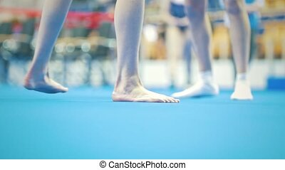 Feet of young woman gymnast competing at the stadium, close...