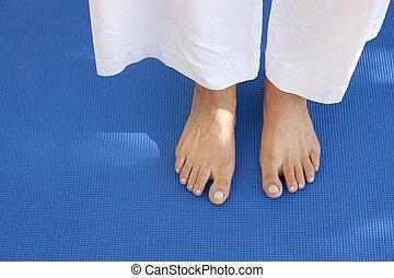 Feet on a blue mat - A womans feet on a training carpet....