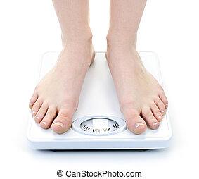 Bare female feet standing on bathroom scale