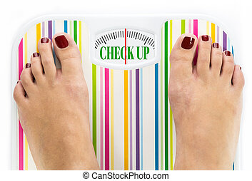 """Feet on bathroom scale with words """"Check up"""" on dial"""