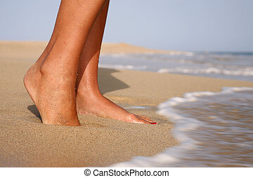 Feet on Beach - Woman standing on a golden beach with waves...