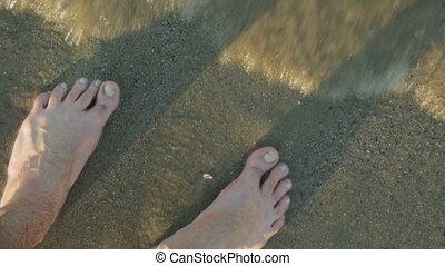 Feet on sand in closeup