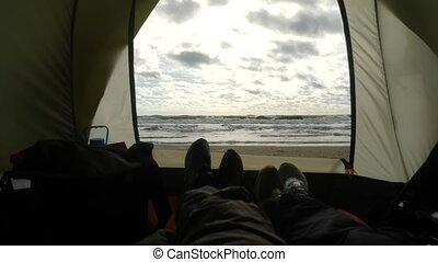feet on the background of a view from a tent on the sea. Camping tent on the beach by the sea. 4k, slow motion.
