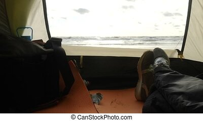 feet on the background of a view from a tent on the sea....