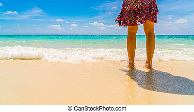 Feet on the sand with Beautiful tropical Maldives island .