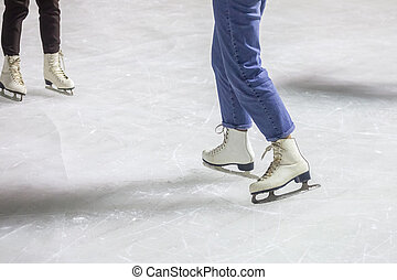 feet on the skates of a person rolling on the ice rink
