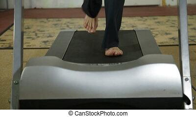 Feet on treadmill - female legs running on treadmill at home