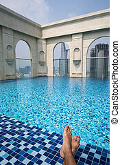 Feet over the sparkling pool on top of building with Saigon aerial view