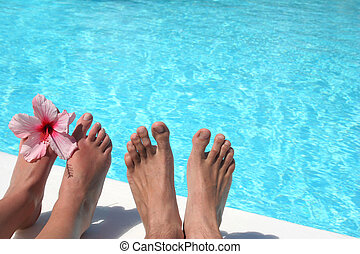 Feet Pool - Man and women's feet by bright pool
