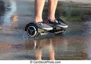 feet ride of a man on a segway on the wet asphalt