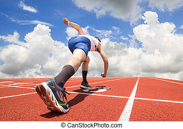Feet runner on start line ready for a sprint start running on track with blue sky background. sport concept.