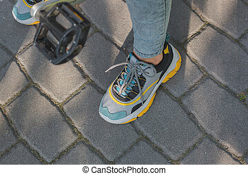 Feet shod in bright sneakers are next to the bicycle pedals